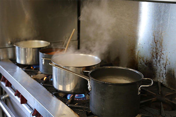 Soup and sauces cooking in pots on stove